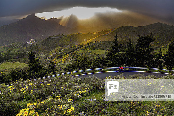 Woman riding electric bicycle on road amidst beautiful mountain landscape