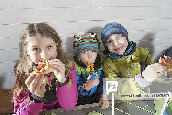 Portrait of children eating pizza