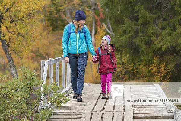 Mother with daughter walking through bridge