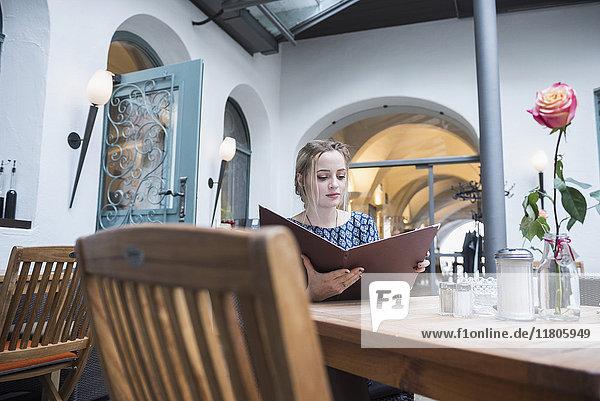 Contemplative young woman holding menu card at restaurant