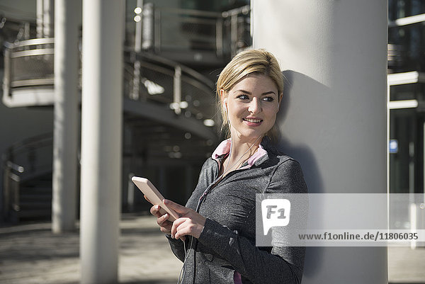 Woman in sportswear listening music on smart phone