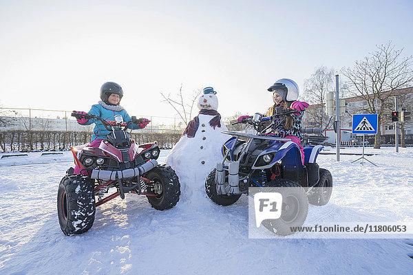 Girls riding quad bike on snow field
