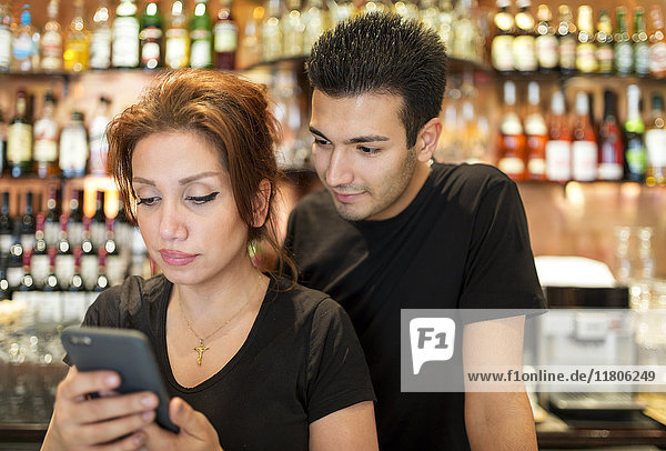 Young couple in bar with cell phone