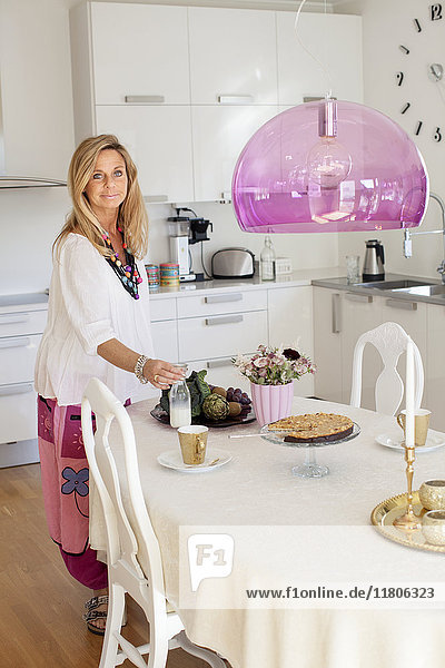 Woman preparing dining table in kitchen