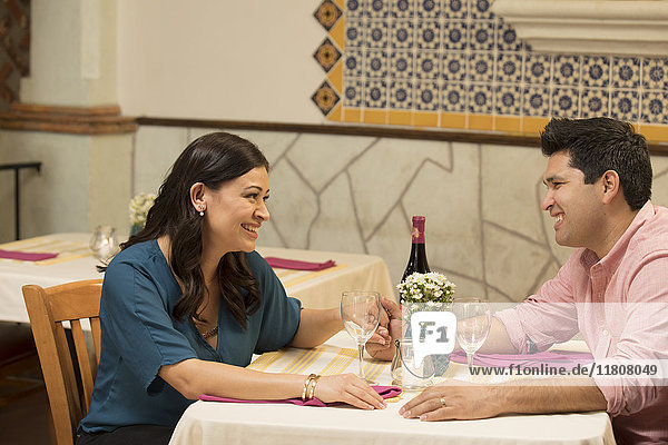 Hispanic couple holding hands at table in restaurant