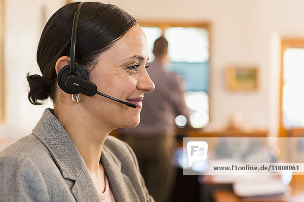 Profile of smiling Caucasian businesswoman wearing headset