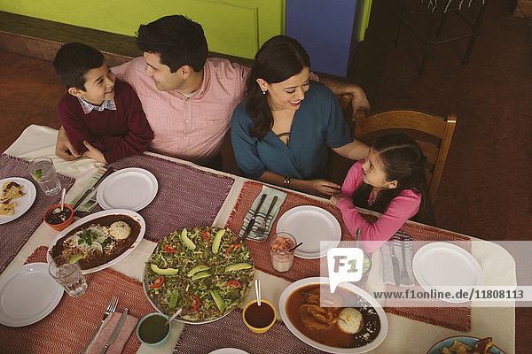 High angle view of Hispanic parents and children in restaurant