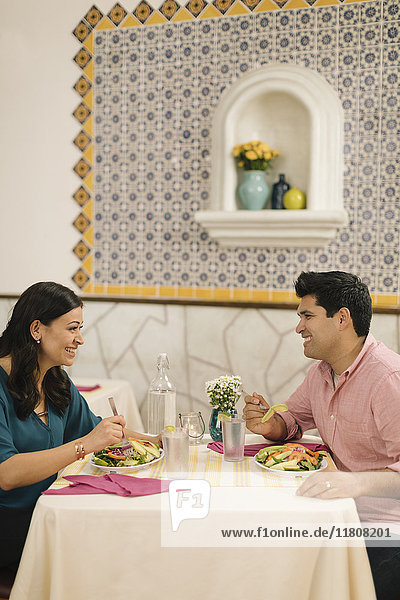 Smiling Hispanic couple eating salad and laughing in restaurant