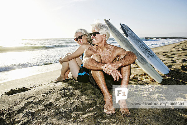Older Caucasian couple sitting on beach with surfboards