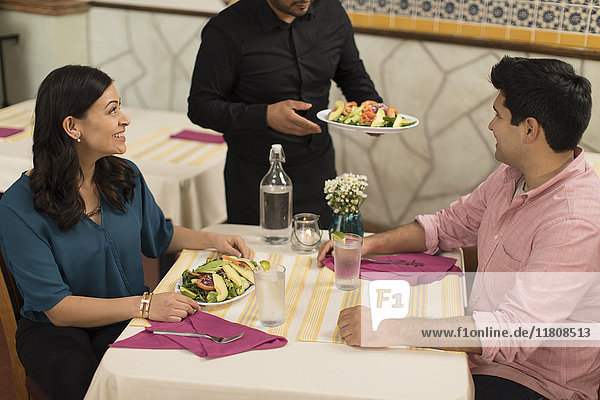 Waiter serving salad to Hispanic couple in restaurant