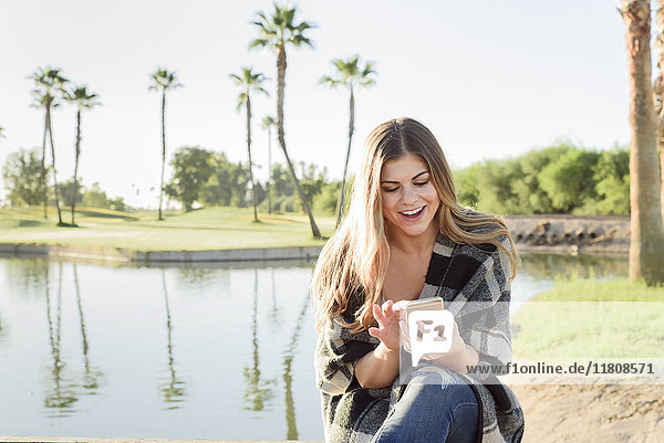 Hispanic woman texting on cell phone near pond