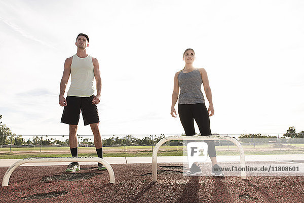 Couple standing nears exercise bars outdoors