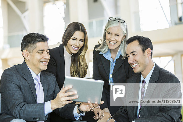 Smiling business people reading digital tablet in lobby