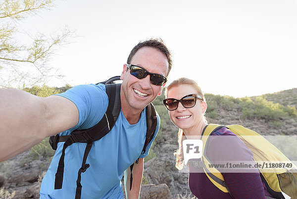 Hikers posing for cell phone selfie