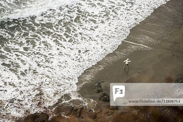 Distant Caucasian woman throwing stone on ocean beach