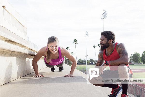 Trainer watching woman do push-ups on bleachers