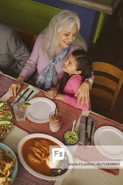 High angle view of grandmother hugging granddaughter in restaurant