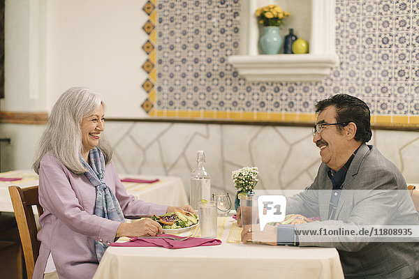 Smiling older couple eating salad and laughing in restaurant