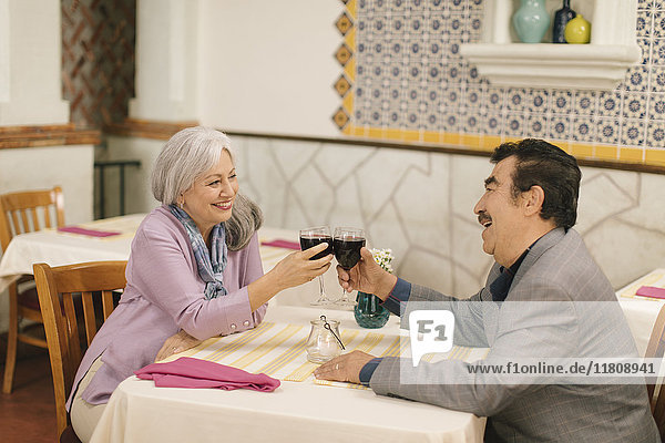 Older couple toasting with wine in restaurant
