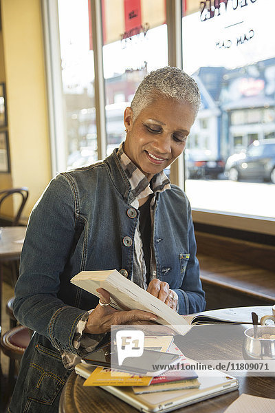 Mixed Race woman reading travel guidebook in coffee shop