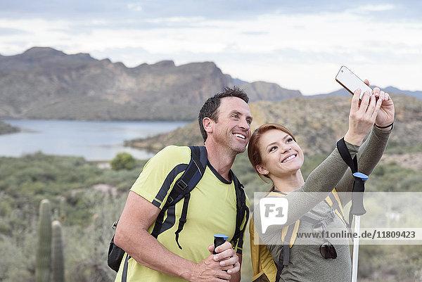 Hikers posing for cell phone selfie in desert