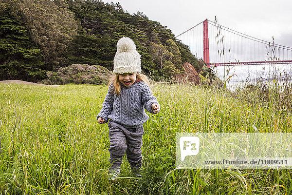 Caucasian girl running in grass near bridge