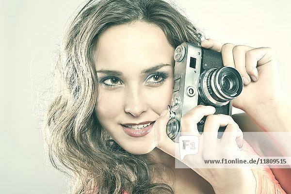 Smiling Caucasian woman holding camera