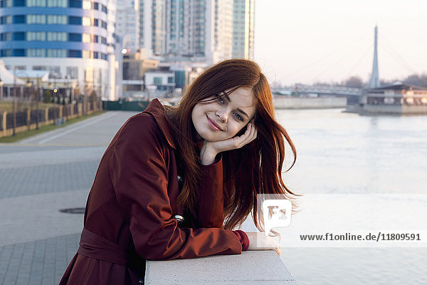 Smiling Caucasian woman leaning on wall at waterfront