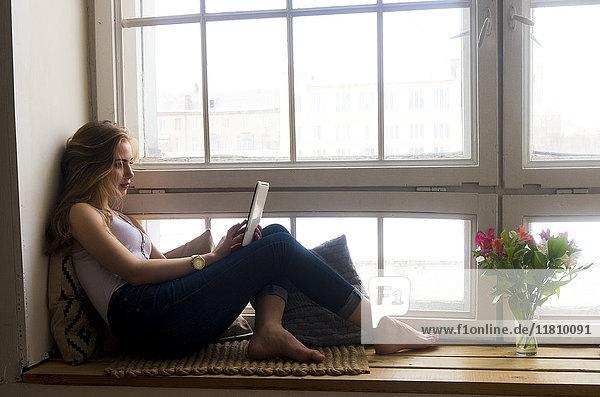 Caucasian woman sitting at window using digital tablet