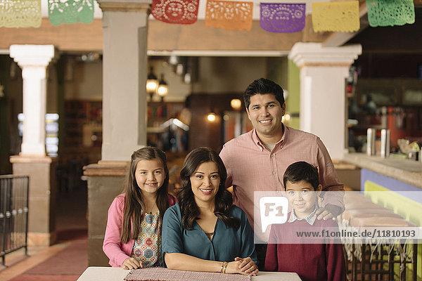 Portrait of smiling Hispanic family in restaurant