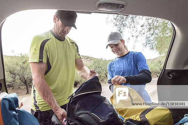 Couple opening backpacks in car
