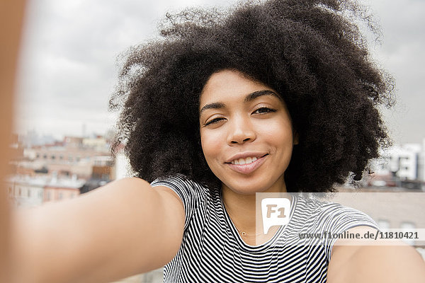 Smiling African American woman posing for selfie on rooftop