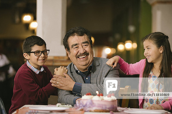 Hispanic grandchildren celebrating birthday of grandfather in restaurant