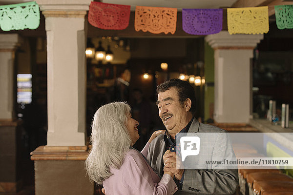 Older couple dancing in restaurant