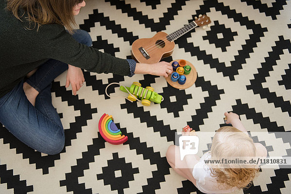 Caucasian mother and daughter sitting on floor playing with toys