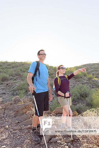 Couple hiking on hill holding walking sticks