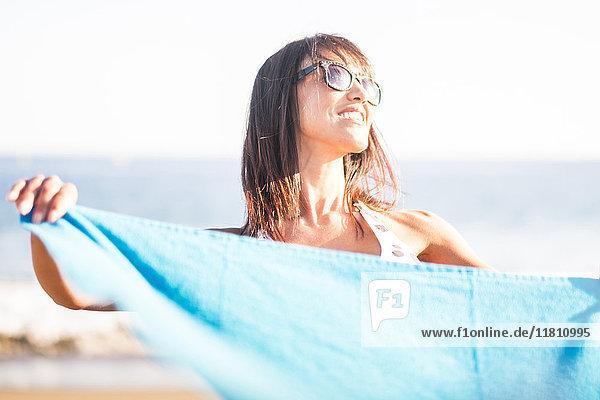 Caucasian woman holding blanket on beach
