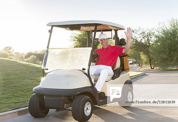 Portrait of Hispanic golfer waving in golf cart