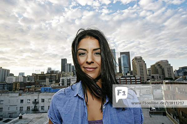 Portrait of smiling Hispanic woman on urban rooftop