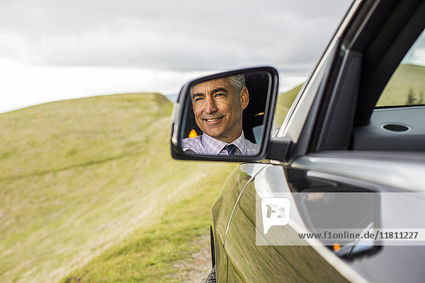 Reflection in mirror of smiling Caucasian businessman driving car