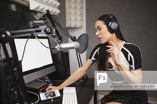 Thai transgender woman using computer and microphone