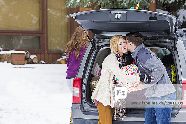 Caucasian man whispering to woman carrying gifts from car in winter