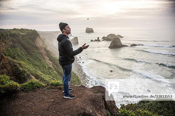 Caucasian man admiring scenic view of ocean sunset