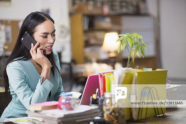 Thai transgender businesswoman talking on cell phone in office