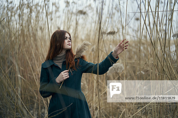 Caucasian woman standing in field touching stalk of grass