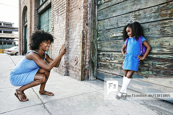 Black mother photographing daughter on sidewalk with cell phone