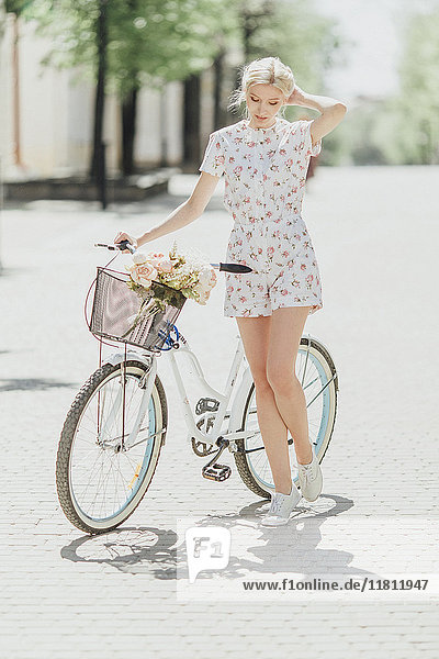 Middle Eastern woman standing near bicycle