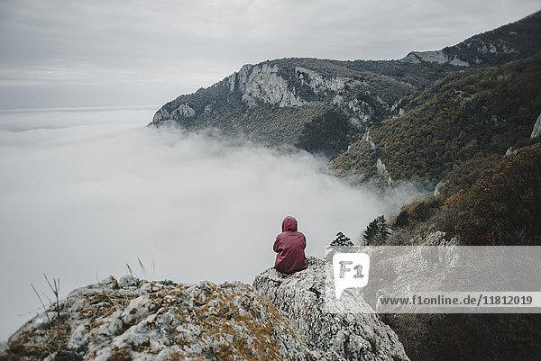 Distant Caucasian woman sitting on rock watching fog on ocean