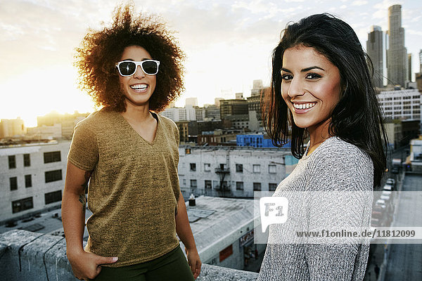 Portrait of smiling Hispanic women on urban rooftop at sunset