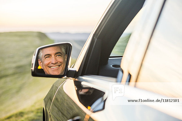 Reflection in mirror of smiling Caucasian man driving car
